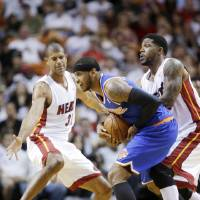 Photo - New York Knicks forward Carmelo Anthony, center, is fouled by Miami Heat forward Udonis Haslem, right, as forward Shane Battier, left, defends during the first half of an NBA basketball game, Sunday, April 6, 2014, in Miami. (AP Photo/Wilfredo Lee)