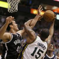 Photo - Brooklyn Nets' Kris Humphries, left, fight for a rebound with Utah Jazz's Derrick Favors during the first half of an NBA basketball game, Saturday, March 30, 2013, in Salt Lake City. (AP Photo/George Frey)