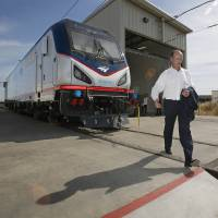 Photo - In this photo taken Saturday, May 11, 2013, Michael Cahill, president of Siemens Rail Systems, walks past one of  the new Amtrak Cities Sprinter Locomotive that was built by Siemens in Sacramento, Calif. The new electric locomotive, one of three of 70 to be built,  will run on the Northeast intercity rail lines and  replace Amtrak locomotives that have been in service for 20 to 30 years.(AP Photo/Rich Pedroncelli)