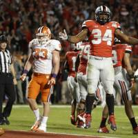 Photo - Ohio State running back Carlos Hyde (34) celebrates after running the ball to the 1-yard line during the second half of the Orange Bowl NCAA college football game against Clemson, Friday, Jan. 3, 2014, in Miami Gardens, Fla. Hyde scored a touchdown on the next play. (AP Photo/Lynne Sladky)
