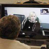 Photo - In this Thursday, Dec. 20, 2012 photo, Dr. Terry Rabinowitz, back to camera, talks with nurse Leslie Orelup at Helen Porter Nursing Home on in Burlington, Vt. New health insurance regulations in Vermont are giving a boost to telemedicine, the system that enables health care providers to offer consult with patients without being in the same room. Telemedicine isn't new, but the new regulations make it easier for physicians to be reimbursed for services performed by two-way video hookups. Fletcher Allen Telemedicine director Dr. Terry Rabinowitz says popular specialties are psychiatry and dermatology. (AP Photo/Toby Talbot)