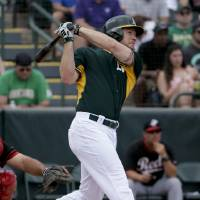 Photo - Oakland Athletics' Brandon Moss watches his three-run home run against the Cincinnati Reds during the second inning of a spring exhibition baseball game in Phoenix, Tuesday, March 25, 2014. (AP Photo/Chris Carlson)