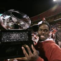 Photo - CELEBRATE, CELEBRATION: Oklahoma Sooners' Adrian Peterson celebrates with the Big 12 Trophy after defeating Nebraska 21-7 in the University of Oklahoma Sooners (OU) college football game against the University of Nebraska Cornhuskers (NU) at Arrowhead Stadium, on Saturday, Dec. 2, 2006, in Kansas City, Mo. by Bryan Terry, The Oklahoman ORG XMIT: KOD