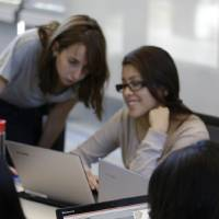 Photo -  Teaching assistant Margarita Sokolova, left, offers help Wednesday during a Girls Who Code class at Adobe Systems in San Jose, Calif. Google is partnering with Girls Who Code, a national nonprofit organization that aims to inspire, educate and equip young women for futures in the computing-related fields. AP Photo   Eric Risberg