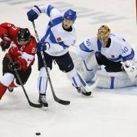 Photo - Canada forward Sidney Crosby battles for the puck against Finland defenseman Olli Maatta in the second period of a men's ice hockey game at the 2014 Winter Olympics, Sunday, Feb. 16, 2014, in Sochi, Russia. (AP Photo/Julio Cortez)