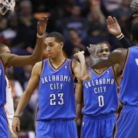 Photo - Oklahoma City Thunder's Kevin Durant (35), Kevin Martin (23), Russell Westbrook (0) and Kendrick Perkins high-five during the second half of an NBA basketball game against the Phoenix Suns, Monday, Jan. 14, 2013, in Phoenix. The Thunder won 102-90. (AP Photo/Matt York) ORG XMIT: PNU112