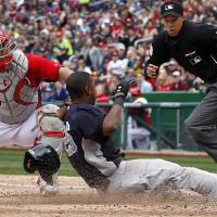 Photo - Washington Nationals catcher Wilson Ramos loses the ball as New York Yankees' Eduardo Nunez slides safely into home with home plate umpire Adam Hamari looking on at right during the fourth inning of an exhibition baseball game at Nationals Park Friday, March 29, 2013, in Washington. (AP Photo/Alex Brandon)