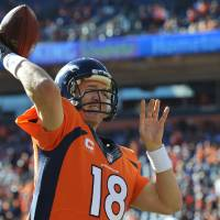 Photo - Denver Broncos quarterback Peyton Manning warms up before the AFC Championship NFL playoff football game against the New England Patriots in Denver, Sunday, Jan. 19, 2014. (AP Photo/Jack Dempsey)