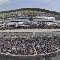 Photo - In this photo taken with a fisheye lens, the field passes the start/finish line during a warmup lap before the STP 500 NASCAR Sprint Cup series auto race at Martinsville Speedway in Martinsville, Va., Sunday April 7, 2013. (AP Photo/Don Petersen)