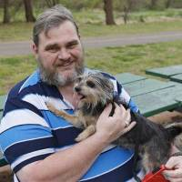 Photo - Jerry Starr is pictured with Tobi, his four-year-old shih tzu-yorkie mix dog at a park in Del City, Okla., Thursday, April 17, 2014. Starr was not allowed to take the dog into a shelter during the May 20, 2013 tornado and opted to stay outside the shelter in his car with his dog. (AP Photo/Sue Ogrocki)