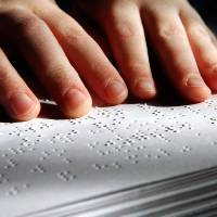 Photo - BLIND / BLINDNESS: Daniel Brookshire, a Tulsa eighth-grader, moves his fingers across words as he reads passages from one of the Braille volumes of the Bible in his family's home  on Thursday, Jan. 7, 2010. Photo by Jim Beckel, The Oklahoman ORG XMIT: KOD