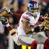 Photo - New York Giants wide receiver Victor Cruz (80) pulls in a pass under pressure from Washington Redskins defensive back Cedric Griffin during the first half of an NFL football game in Landover, Md., Monday, Dec. 3, 2012. (AP Photo/Evan Vucci)