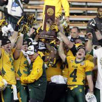 Photo - FILE – In this Jan. 4, 2014 file photo, North Dakota State players celebrate with the trophy after beating Towson 35-7 in the FCS championship NCAA college football game in Frisco, Texas. The poll of league coaches, media and sports information directors released Tuesday, July 29, 2014, has NDSU picked to win the Missouri Valley Football Conference title this season. South Dakota State is picked to finish second in the conference. (AP Photo/Tony Gutierrez, File)