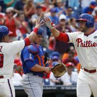 Photo - Philadelphia Phillies' Darin Ruf, right, and Carlos Ruiz, left, celebrate in front of  New York Mets catcher Anthony Recker after Ruff's two-run home run during the fourth inning of a baseball game, Monday, Aug. 11, 2014, in Philadelphia. (AP Photo/Matt Slocum)