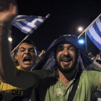 Photo - Greece soccer supporters celebrate their team's win in a World Cup soccer match in front of the city's landmark of White Tower, in the northern Greek port of Thessaloniki, on Wednesday, June 25, 2014. Greece won Ivory Coast 2-1 to advance to the round of 16 for the first time in their World Cup history. (AP Photo/Nikolas Giakoumidis)