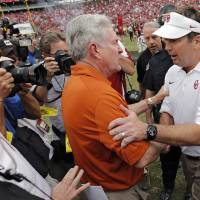 Photo - Bob Stoops and Mack Brown meet at midfield after the Sooners' 63-21 win over Texas during the Red River Rivalry college football game between the University of Oklahoma (OU) and the University of Texas (UT) at the Cotton Bowl in Dallas, Saturday, Oct. 13, 2012. Photo by Chris Landsberger, The Oklahoman