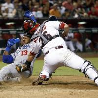 Photo - Los Angeles Dodgers shortstop Hanley Ramirez (13) slides home safely in front of Arizona Diamondbacks catcher Miguel Montero (26) in the seventh inning during a baseball game, Tuesday, Aug. 26, 2014, in Phoenix. (AP Photo/Rick Scuteri)