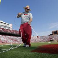 Photo - Jeff Salmond, Director of Athletics Fields, takes his turn as roundskeepers paint the field in preparation for Saturday's season opener for the University of Oklahoma Sooners at Gaylord Family-Oklahoma Memorial Stadium in Norman, Okla., on Wednesday, Aug. 28, 2014. Photo by Steve Sisney, The Oklahoman