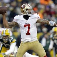 Photo - San Francisco 49ers quarterback Colin Kaepernick (7) throws a pass during the first half of an NFL wild-card playoff football game against the Green Bay Packers, Sunday, Jan. 5, 2014, in Green Bay, Wis. (AP Photo/Jeffrey Phelps)