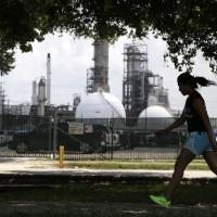Photo - A teenage girl walks around the track of a park across the street from the Valero refinery Monday, Aug. 4, 2014, in the Manchester neighborhood of Houston. An Environmental Protection Agency rule to require refineries to monitor emissions of benzene is to be publicly debated Tuesday near Houston. (AP Photo/Pat Sullivan)