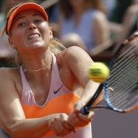 Photo - Russia's Maria Sharapova returns the ball to Romania's Simona Halep during their final match of  the French Open tennis tournament at the Roland Garros stadium, in Paris, France, Saturday, June 7, 2014. (AP Photo/Michel Euler)