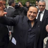 Photo - In this frame made from video footage made available by APTN, former Premier Silvio Berlusconi waves to supporters outside his residence, in Rome, Saturday, April 27, 2013. Berlusconi says he thinks Italy will finally get a government Saturday, a broad coalition that brings his conservatives back in power. The media mogul also told journalists in Rome Saturday he wouldn't be part of the Cabinet headed by a center-left leader Enrico Letta. (AP Photo/via APTN)