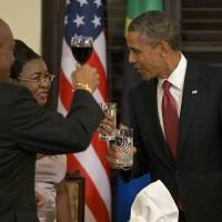 Photo - President Barack Obama toasts with Tanzanian first lady Salma Kikwete during an official dinner at the State House in Dar Es Salaam, Tanzania, Monday, July 1, 2013. The president is traveling in Tanzania on the final leg of his three-country tour in Africa. (AP Photo/Evan Vucci)