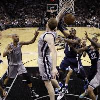 Photo - Memphis Grizzlies' Mike Conley (11) is defended by San Antonio Spurs' Matt Bonner, center, as he tries to score during the first half in Game 1 of a Western Conference Finals NBA basketball playoff series Sunday, May 19, 2013, in San Antonio. (AP Photo/Eric Gay)