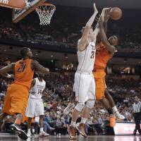 Photo - Oklahoma State's Le'Bryan Nash (2) is defended by Texas' Connor Lammert (21) as he tries to shoot during the second half of an NCAA college basketball game, Saturday, Feb. 9, 2013, in Austin, Texas. Oklahoma State won 72-59. (AP Photo/Eric Gay) ORG XMIT: TXEG112