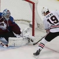 Photo - Colorado Avalanche goalie Semyon Varlamov, left, of Russia, makes a pad save of a shot off the stick of Chicago Blackhawks center Jonathan Toews in the first period of an NHL hockey game in Denver on Wednesday, March 12, 2014. (AP Photo/David Zalubowski)