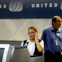 Photo - FILE - In this Friday, June 17, 2011, file photo, a United Airlines employee staffs a ticketing counter at San Francisco International Airport, in San Francisco. United Airlines said, Jan. 16, 2014, it will furlough 688 flight attendants after it didn't get enough people to take a voluntary buyout. (AP Photo/Noah Berger, File)