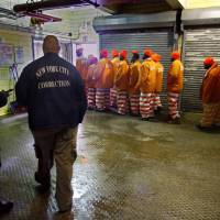 Photo - FILE - In this March 16, 2011 file photo, inmates file out of the prison bakery at the Rikers Island jail after working the morning shift, in New York.  A recent report issued by the Independent Budget Office found it cost $167,731 in 2012 to house 12,287 daily New York City inmates. New York City pays almost as much to jail an inmate in a year as it would to pay a student's four years of tuition at a private college. (AP Photo/Bebeto Matthews, File)