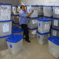 Photo - An electoral worker carries ballot boxes at a counting center in Baghdad, Iraq, Sunday, April 21, 2013. Iraqis have begun counting votes from the first provincial elections since the last U.S. troops withdrew in December 2011. (AP Photo/ Karim Kadim)