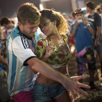 Photo - A woman from Brazil and a man from Argentina dance samba at the World Cup Fan Fest 2014, on Copacabana beach, in Rio de Janeiro, Brazil, Wednesday, July 9, 2014. The flood of foreign football fans, the vast majority of them men, has been a boon for the single ladies of Brazil, where a demographic imbalance means women outnumber men by more than 4 million nationally. (AP Photo/Silvia Izquierdo)
