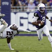 Photo - TCU quarterback Trevone Boykin (2) rushes past Samford linebacker Justin Cooper (23) in the first half of an NCAA college football game in Fort Worth, Texas, Saturday, Aug. 30, 2014. (AP Photo/Jim Cowsert)