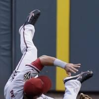 Photo - Arizona Diamondbacks left fielder David Peralta rolls on the ground after catching a fly ball hit by Cincinnati Reds' Brayan Pena in the fourth inning of a baseball game, Monday, July 28, 2014, in Cincinnati. (AP Photo/Al Behrman)