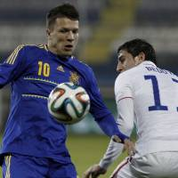 Photo - Yevhen Konoplianka, left, of Ukraine controls the ball with Alejandro Bedoya of U.S. during an international friendly match at Antonis Papadopoulos stadium in southern city of Larnaca, Cyprus, Wednesday, March 5, 2014.  The Ukrainians are facing the United States in a friendly on Wednesday in Cyprus, a match moved from Kharkiv to Larnaca for security reasons. (AP Photo/Petros Karadjias)