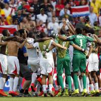 Photo - Costa Rican players celebrate after the group D World Cup soccer match between Italy and Costa Rica at the Arena Pernambuco in Recife, Brazil, Friday, June 20, 2014. Costa Rica won the match 1-0. (AP Photo/Frank Augstein)