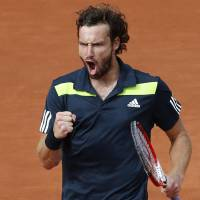 Photo - Latvia's Ernests Gulbis clenches his fist after scoring a point during the quarterfinal match of the French Open tennis tournament against Tomas Berdych of the Czech Republic at the Roland Garros stadium, in Paris, France, Tuesday, June 3, 2014.  (AP Photo/Darko Vojinovic)