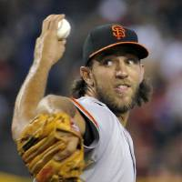 Photo - San Francisco Giants pitcher Madison Bumgarner throws against the Arizona Diamondbacks during the second inning of a baseball game on Sunday, June 22, 2014, in Phoenix. (AP Photo/Matt York)