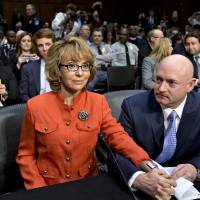 Photo - FILE - In this Jan. 30, 2013 file photo, former former U.S. Rep. Gabrielle Giffords, who survived a gunshot to the head in 2011, during a mass shooting in Tucson, Ariz., sits ready with her husband, retired astronaut Mark Kelly, at a Senate Judiciary Committee hearing on Capitol Hill in Washington to discuss legislation to curb gun violence.  Giffords and Kelly are scheduled to be in Denver, Monday, March 4, 2013 to testify in support of at least one of the seven gun-control bills being considered by the Colorado Legislature. Eileen McCarron, president of the Colorado Ceasefire Capitol Fund, says Kelly will speak in support of a House bill that requires all private gun sales and transfers to be subject to a background check. (AP Photo/J. Scott Applewhite, File)