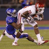 Photo - Kansas' Anthony Davis (30) tries to stop Oklahoma's Jaz Reynolds (16) during the college football game between the University of Oklahoma Sooners (OU) and the University of Kansas Jayhawks (KU) on Saturday, Oct. 15, 2011. in Lawrence, Kan. Photo by Chris Landsberger, The Oklahoman