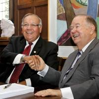 Photo - Chief George Tiger of the Muscogee (Creek) Nation, left, and David Boren, president of the University of Oklahoma, smile as they shake hands after signing documents in which the University of Oklahoma transferred ownership of the George Nigh Rehabilitation Center in Okmulgee to the Muscogee (Creek) Nation during a  ceremony in Boren's office on Monday.  The two men were seated at a table used by Boren in his Washington office when he served as a U.S. senator before becoming the university's president.  Photo  by Jim Beckel, The Oklahoman.  Jim Beckel