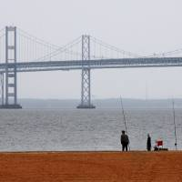 Photo - FILE - In this Wednesday, May 12, 2010, file photo, a man looks out over the Chesapeake Bay, with the Bay Bridge in the background, at Sandy Point State Park in Annapolis, Md. A federal court is deciding whether the Obama administration's plan to clean up the Chesapeake Bay watershed oversteps legal bounds, an election-year appeal by farmers and 21 attorneys general that could shape future U.S environmental policy. (AP Photo/Jacquelyn Martin, File)