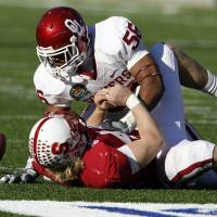 Photo - Ronnell Lewis (56) disrupts a pass intended for Owen Marecic (48) during the second half of the Brut Sun Bowl college football game between the University of Oklahoma Sooners (OU) and the Stanford University Cardinal on Thursday, Dec. 31, 2009, in El Paso, Tex.   Photo by Steve Sisney, The Oklahoman ORG XMIT: KOD
