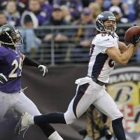 Photo - Denver Broncos wide receiver Eric Decker pulls in a touchdown pass as Baltimore Ravens cornerback Cary Williams looks on during the second half of an NFL football game in Baltimore, Sunday, Dec. 16, 2012. (AP Photo/Nick Wass)