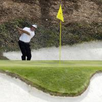 Photo - Phil Mickelson hits out of a bunker on the 12th hole during the second round of the Masters golf tournament Friday, April 11, 2014, in Augusta, Ga. (AP Photo/Charlie Riedel)