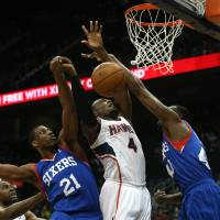 Photo - Atlanta Hawks forward Paul Millsap (4) attempts a shot as he is defended Philadelphia 76ers forward Thaddeus Young (21) and Philadelphia 76ers forward Jarvis Varnado (40) in the first half of an NBA basketball game Monday, March 31, 2014, in Atlanta. (AP Photo/Jason Getz)