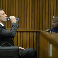 Photo - Oscar Pistorius, takes a sip of water in court at his murder trial in Pretoria, South Africa, Friday, Aug. 8, 2014. Final arguments by the defense entered a second day in his murder trial of the once-celebrated athlete who fatally shot his girlfriend, Reeva Steenkamp, through a toilet cubicle door in his home on Valentine's Day last year. (AP Photo/ Herman Verwey, Pool)