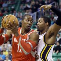 Photo - Utah Jazz's Derrick Favors, right, defends against Houston Rockets' Dwight Howard in the first quarter of an NBA basketball game Monday, Dec. 2, 2013, in Salt Lake City. (AP Photo/Rick Bowmer)